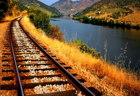 Railroad alongside to river - clouds, blue, peaceful, alongside, nice, cottages, mountain, train, nature, view, riverbank, lovely, grass, village, calm, railway, shore, together, water, houses, cabins, summer, railroad, lakeshore, beautiful, pretty, river, sky, reflection