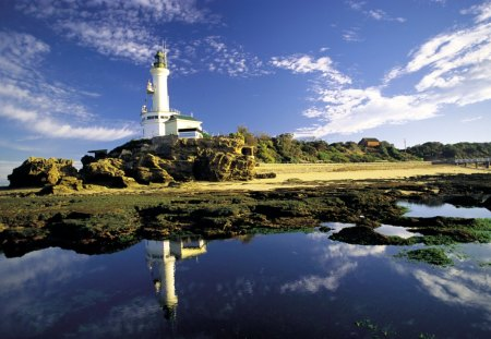 fantastic lighthouse reflected - hill, bridge, shore, rocks, sea, lighthouse