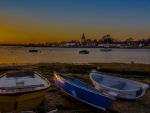 rowboats on a harbor shore at sunset