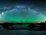 aurora borealis and the milky way above a lake