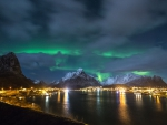 northern lights over a bayside village at night