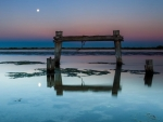 moon over broken seashore pier