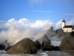 waves crashing around a lighthouse on a rocky shore