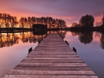 wooden pier on a calm lake at sunset hdr