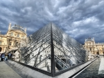 the louvre glass pyramid under cloudy sky hdr