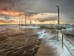 sea waves overflowing pier at sunset hdr