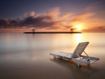 lounge chair in a shallow sea at sunset
