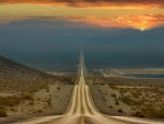 long desert alley highway at sunset
