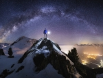 man standing on a mountain peak under stars