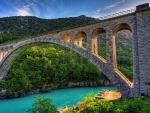stone arch bridge over turquoise river hdr