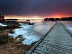 pier on a frozen lake at sunset
