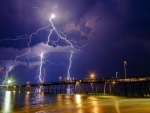 lightning strikes beyond sea pier