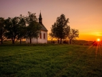 little chapel on a grassy hill at sunset