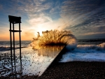 waves crashing on a beach pier at sunset