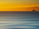 lighthouse on a blue carpet sea at sunset