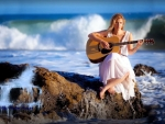 girl strumming guitar in a sea cliff