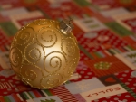 Golden Bauble on Christmas Wrapping Paper