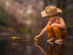 Little boy playing with yellow frogs