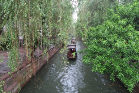 The small boat is rocking on the river - China, tour, river, boat, willow trees