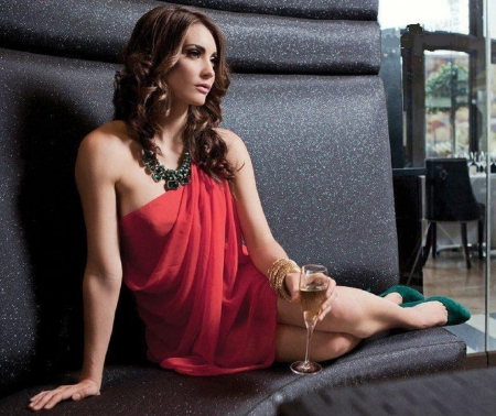 Tanit Phoenix - green high heels, see thru, bracelets, posing on corner seat, tall glass, brunette, large necklace, red sheer dress